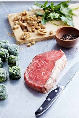 An arrangement of beef steak, frozen vegetables and nuts