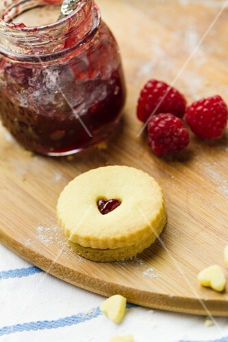 Homemade Jammie Dodgers and raspberry jam on a floured wooden board