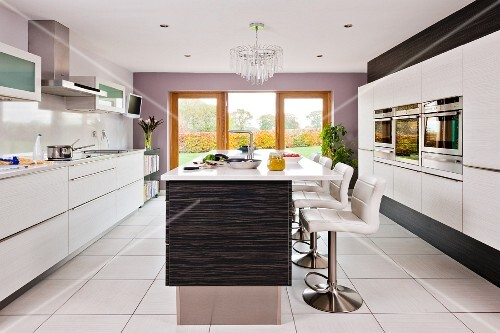 A contemporary kitchen in white with barstools at an island counter on a white tiled floor