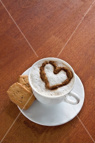 A cup of coffee decorated with a milk foam heart