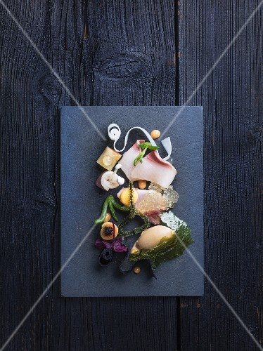 A hamachi platter with seaweed and a side of vegetables