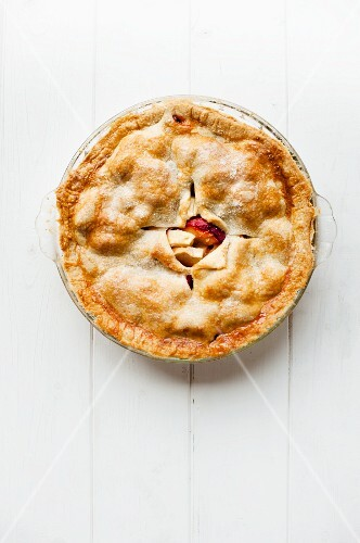 A whole plum pie in a glass dish seen from above
