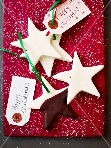Star-shaped peppermint cream biscuits as gift tags on a red surface