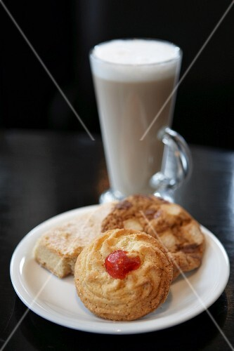 Three different biscuits on a plate with a latte macchiato in the background