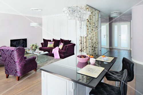 A cool living area with purple upholstered furniture, silver birch trunks in a glass case and, in the foreground, a bar with black leather stools