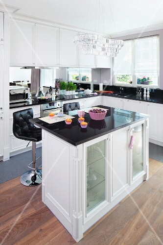 An island counter in an elegant fitted kitchen with a crystal pendant light and lilac coloured baking moulds on a reflective work surface