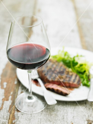 A glass of red wine in front of a grilled beef steak with salad