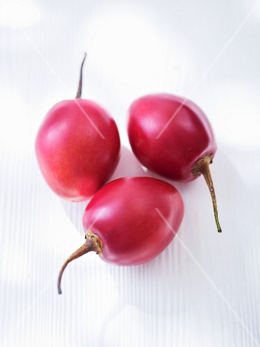 Three tamarillos on a white wooden surface