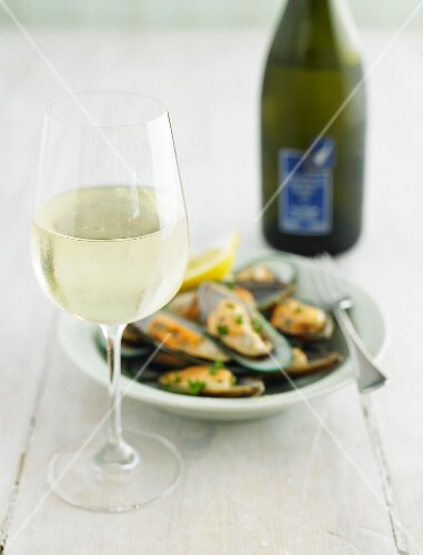 A glass of white wine with a mussel dish and a bottle of wine in the background out of focus