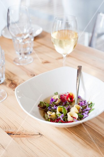 Chicken tortellini in a vegetable broth with edible flowers