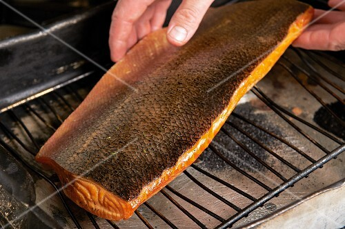 A chef placing a pan-smoked salmon fillet on a wire cooling rack