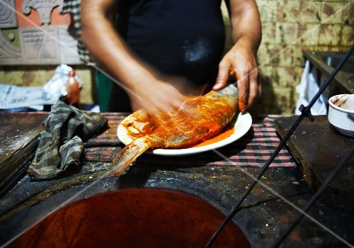 A man preparing tandoori-masala fish