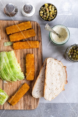 A fish finger sandwich with tartare sauce and capers being made