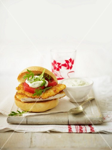 A breaded chicken breast, tomato and a dip as a burger