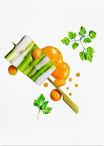 A spring onion skewer with pepper sauce and chervil