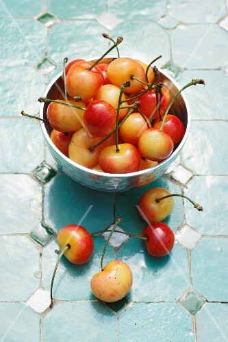Yellow cherries in a metal bowl and next to it