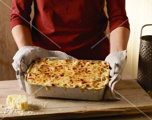 A woman holding a dish of freshly baked lasagne
