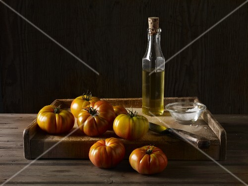 Marmande tomatoes on a wooden board with olive oil, salt and a knife