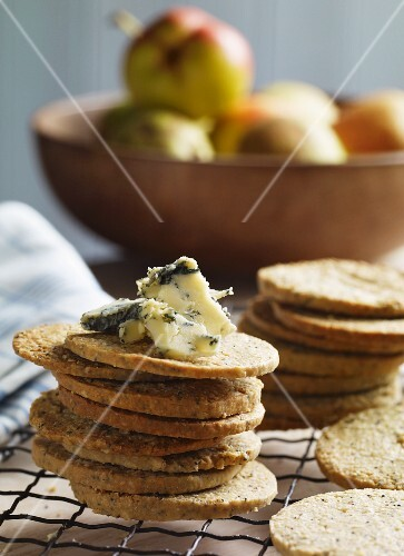 A stack of poppy seed and oat biscuits with Stilton with a bowl of pears in the background