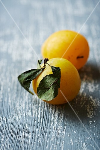 Yellow plums with dried leaves