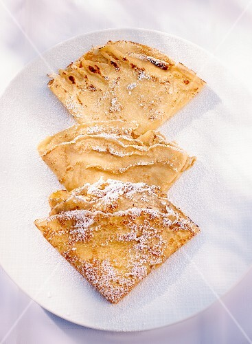 Three folded crepes dusted with icing sugar