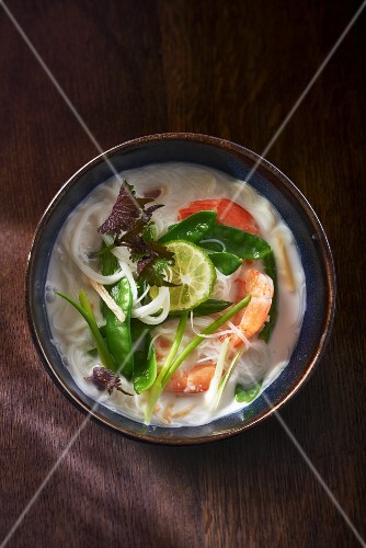 Coconut and rice noodle soup with vegetables and prawns
