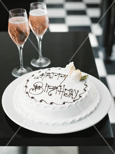 A white birthday cake and rosé champagne