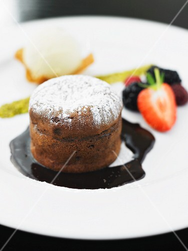 Chocolate soufflé with icing sugar and chocolate sauce