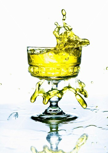 A yellow drink splashing from a glass
