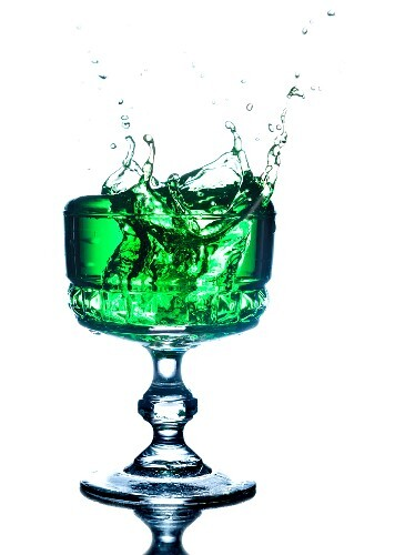 A green drink splashing out of a glass