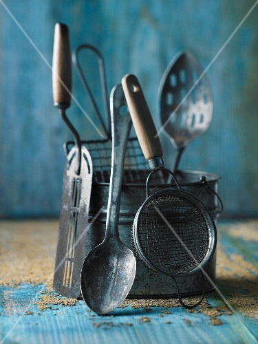 Various antique kitchen utensils on a blue wooden surface