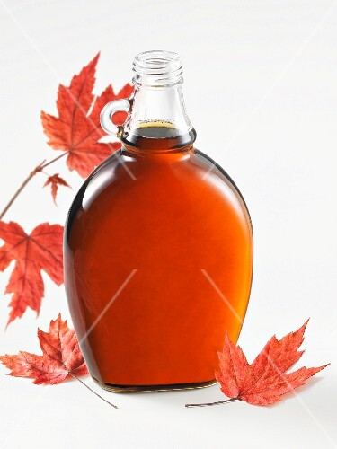 A bottle of maple syrup and autumnal leaves