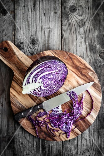 Sliced red cabbage on a chopping board with a knife