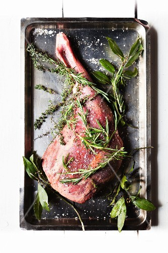 Fresh leg of venison with herbs, salt and pepper on a baking tray