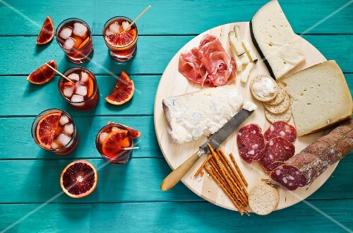 An Italian appetiser platter next to glasses of aperitifs garnished with slices of blood orange