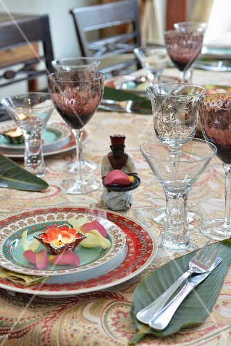 An exotically laid table with crystal glasses, banana leaves, tea lights and petals