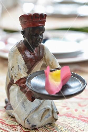 Small ceramic figurine holding scented petals