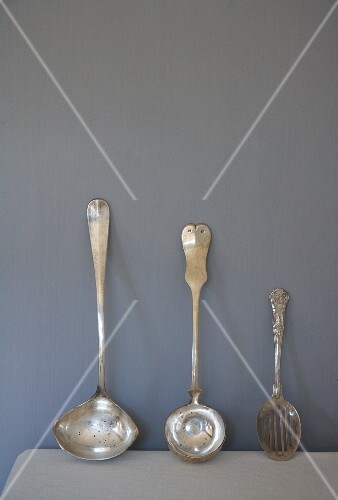 Antique silver ladles and slotted spoon leaning on wall
