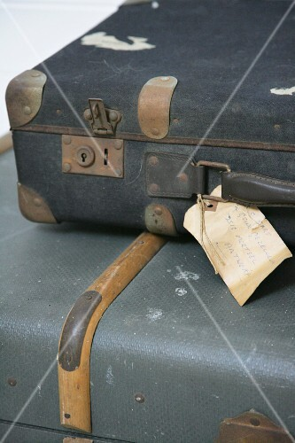 Two old suitcases with faded paper tags