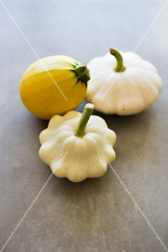 Two white patty pan squashes and a yellow summer squash on a grey surface