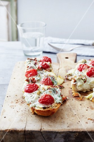 Slices of baguette topped with tomatoes, mozzarella and gorgonzola