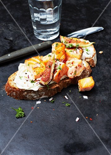 A slice of bread topped with salmon, cream cheese, figs and herbs