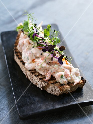 An open sandwich topped with prawn salad