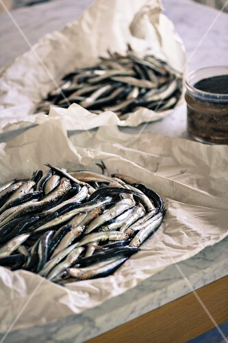 Fresh sardines in packing paper on a marble-topped kitchen table