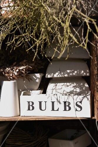 Stacks of plant pots on a shelf behind a white box with a label