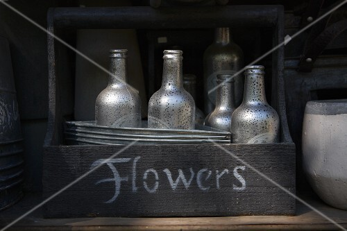 An old wooden basket with a label filled with silver-painted bottles