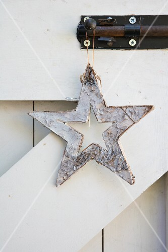 A star made from white-painted tree bark hanging from a bolt on a wooden gate