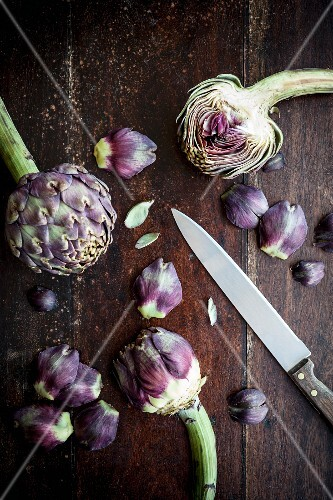 Artichokes, a knife and individual artichoke leaves on a wooden surface