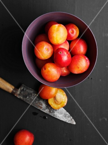 A bowl of plums next to a knife