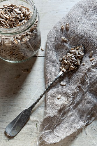 Sunflower seeds on a sliver spoon on a piece of jute
